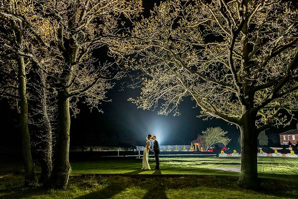 bride and groom kissing at night under trees