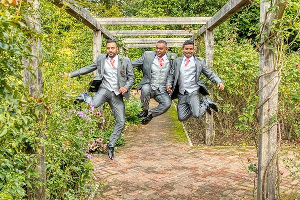 groom best man and groomsman jumping