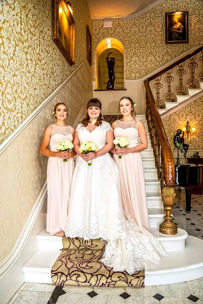 bride on grand staircase with her bridesmaids
