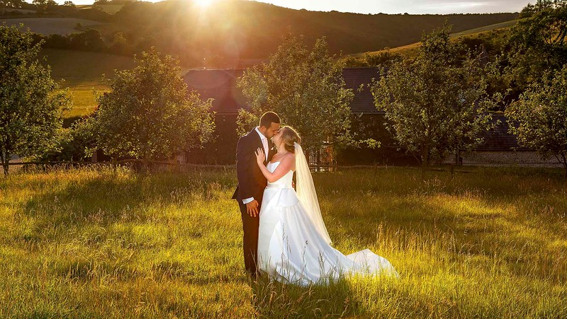 bride and groom kissing in a field at sunset
