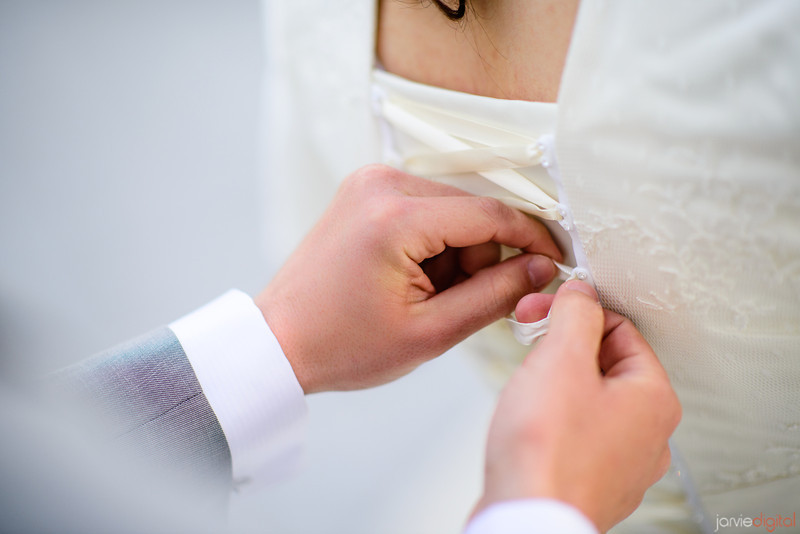 Groom helping with brides dress during First look pictures at the Timpanogos Temple