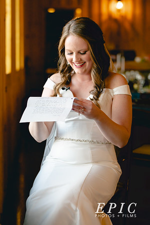 Bride sitting near window, reading a letter from her Groom