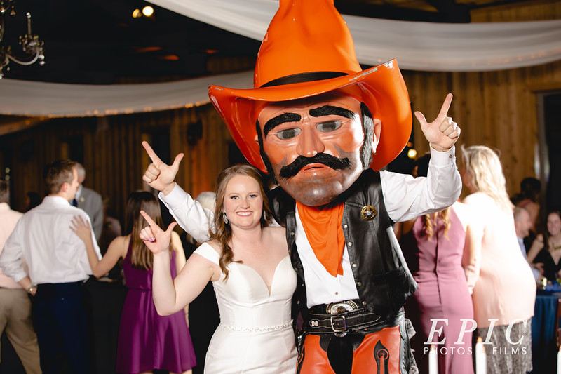 The OSU mascot, Pistol Pete, crashes the reception and is taking a picture with the bride