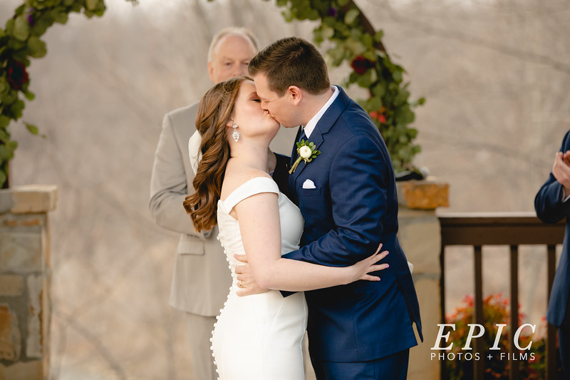 Bride and groom share their first kiss at the altar