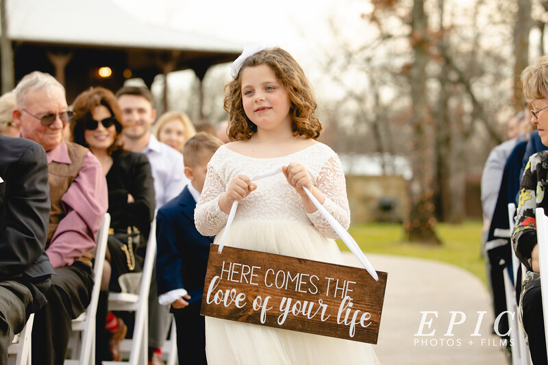 "Flower girl walks down the aisle holding a sign that reads ""Here comes the love of your life"""