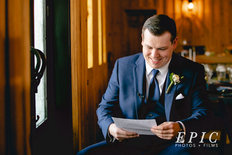 Groom sits near window, reading a letter from his bride