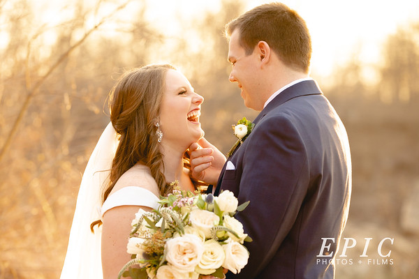 Bride and groom share a laugh in front of a beautiful golden sunset