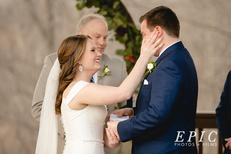 Bride wipes a tear from her grooms cheek while they are at the altar reading their vows to each other