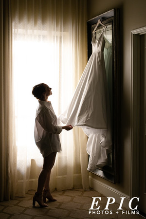 Bride looks at her dress on her wedding day at the Adolphus Hotel