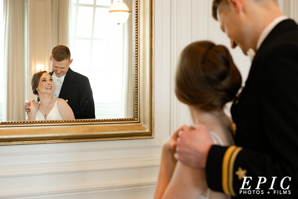 Bride and groom smiling in the mirror reflection