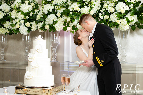 Bride and groom kiss in front of their wedding cake