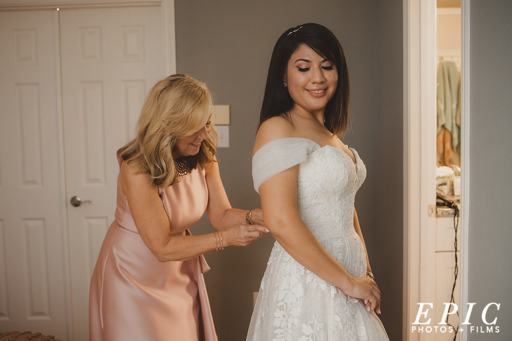 Getting the brides dress on during wedding preperations in dallas texas
