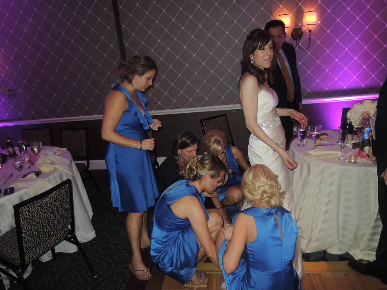 Bridesmaids making an emergency repair to Emily's dress.