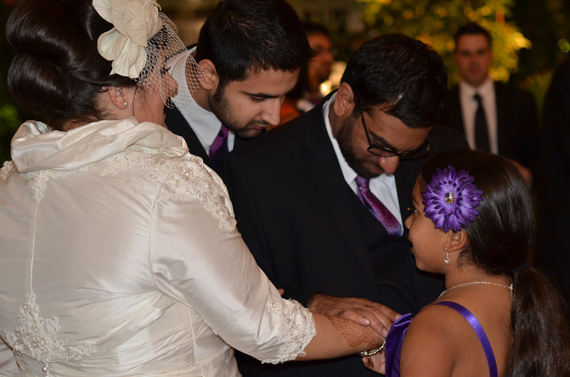 Amar is trying to find his initials in Nicole's henna...