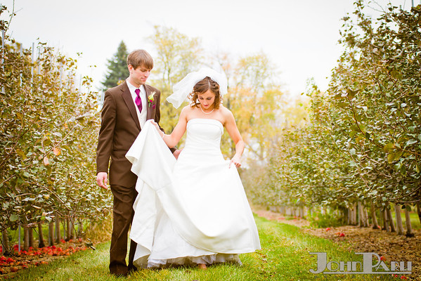 bride holding wedding dress while walking with groom in apple orchard