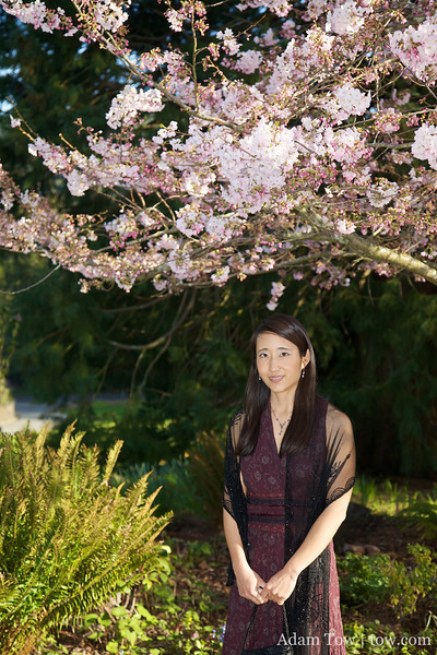 Rae standing by a cherry blossom tree