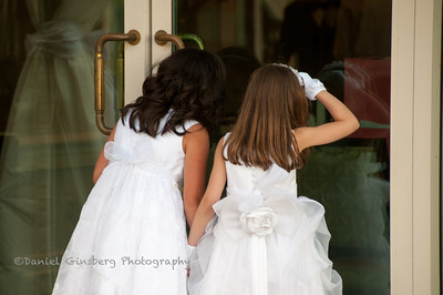 Two girls look through a glass door at the bride before the wedding.