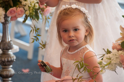 Flower girl in a row of white chairs.