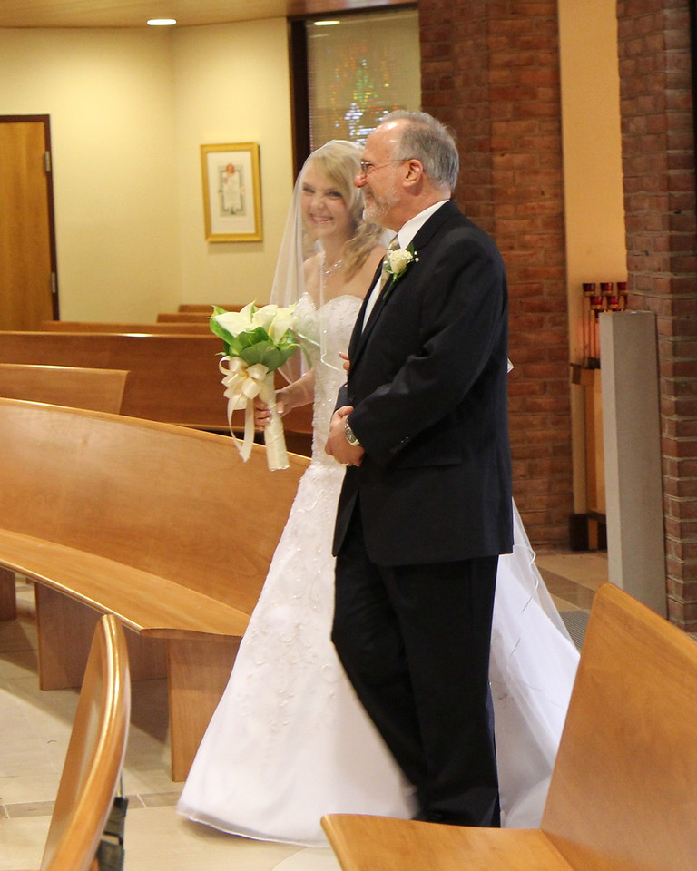 Beaming bride Glencora enters St. Mary's Church with her proud father.