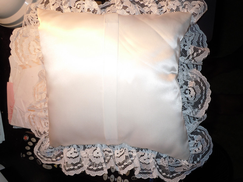 **Unavailable**<br /> <br /> I have a plain white ring pillow, not in package.  It is a satin finish with lace edging and a simple fabric band underneath for the ring bearer to hold the pillow. $2