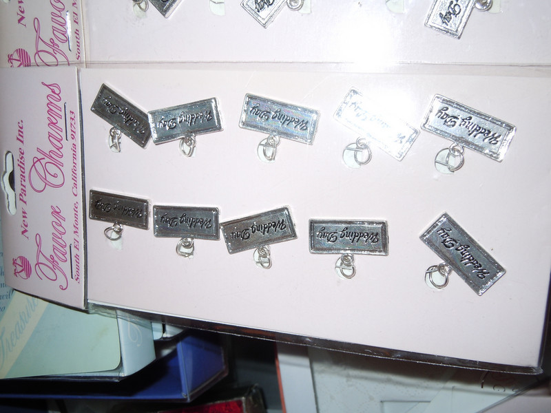 "Close up of the charms<br /> <br /> Metal Wedding charms, 10 pcs.  Each piece reads ""wedding day"", 4 packages available, $1"