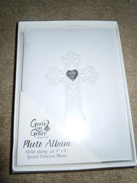 White album with embossed cross and heart stone in the center, $2