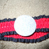 small red with black edging with a silver cardboard circle attached to the front, 25 cents