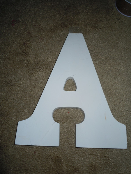 """Close up of A<br /> <br /> white wooden letters, 9"""" tall, 5 3/4"""" wide, $2 each"""