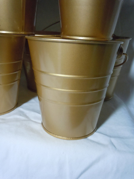 Close up of gold bucket<br /> metallic gold Metal Buckets with gold metal handle. They are about 4 inches in height, 4 inches on the opening, and 2 7/8 inches on the bottom. 10 available. $1 each or all 10 for $8