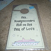 "Plastic laminated door hanger, ""Shh...Honeymooners still on the sea of love"". 4"" x 8 1/4"". $.50, 1 available"