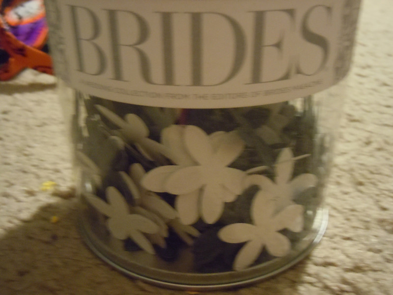 One unopened package of BRIDES floral confetti.  The packaging looks like a clear plastic paint can, however the handle is no longer attached.  There are cardstock confetti inside, shimmery white and black flowers.  There is 1 oz in the can.  one available, $3