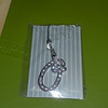 "Jeweled pendant/tie on: 1 1/2"" tall x 1 1/4"" wide, one O initial available, $2"