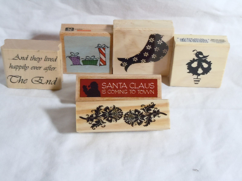 Wooden Rubber Stamps<br /> 3 presents, NEW, $1<br /> bird with design, NEW, $1<br /> Partridge in a pear tree, NEW, $1<br /> And they live happily ever after THE END, Used $1<br /> Santa Claus is Coming to Town, NEW, $1<br /> Scrolls, NEW, $1