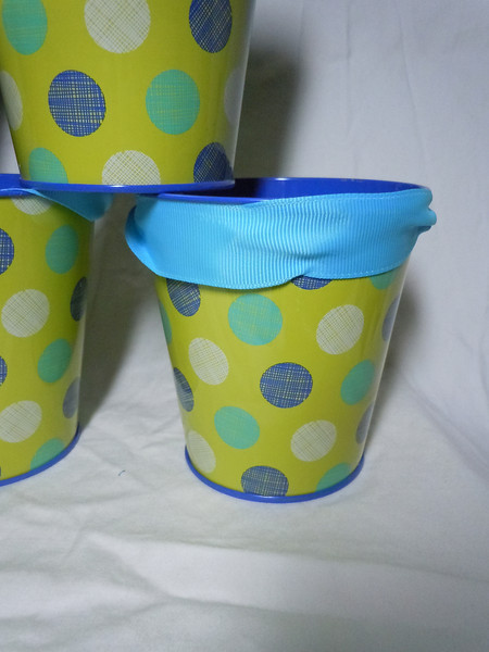 Close up of bucket<br /> green with blue, white, teal dotted Metal Buckets with Blue grosgrain ribbon handle. They are about 4 inches in height, 4 inches on the opening, and 2 7/8 inches on the bottom. 10 available. $1 each or all 10 for $8