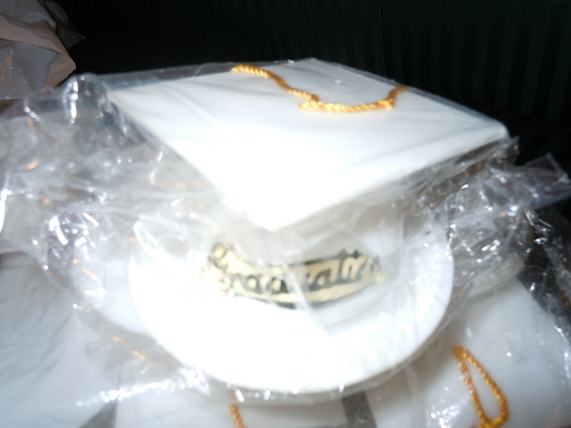 """close up of cap.<br /> <br /> Brand New: white graduation caps that can be table decoration, favors, or cake decorations. The bottom piece is about 3 1/4"""" in diameter and is removable from the cap itself. The cap is about 2 1/4"""" with a gold tassel and gold wording attached that reads Graduation in cursive. There are 12 total in the package. Whole Package is $4. Only one package available"""