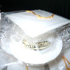 "close up of cap.<br /> <br /> Brand New: white graduation caps that can be table decoration, favors, or cake decorations. The bottom piece is about 3 1/4"" in diameter and is removable from the cap itself. The cap is about 2 1/4"" with a gold tassel and gold wording attached that reads Graduation in cursive. There are 12 total in the package. Whole Package is $4. Only one package available"