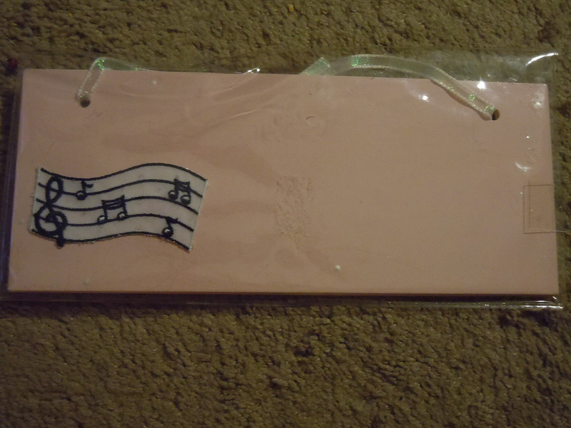 Wooden sign, diy<br /> It is light pink, with a shimmery translucent ribbon to hang it.  There is a musical sheet notes on the left lower corner.  The package is new, includes silver stickers. One available, $2