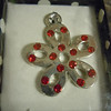 Prima Marketing pendant: item # 511227, flower pendant with red gems. one available, $2 each