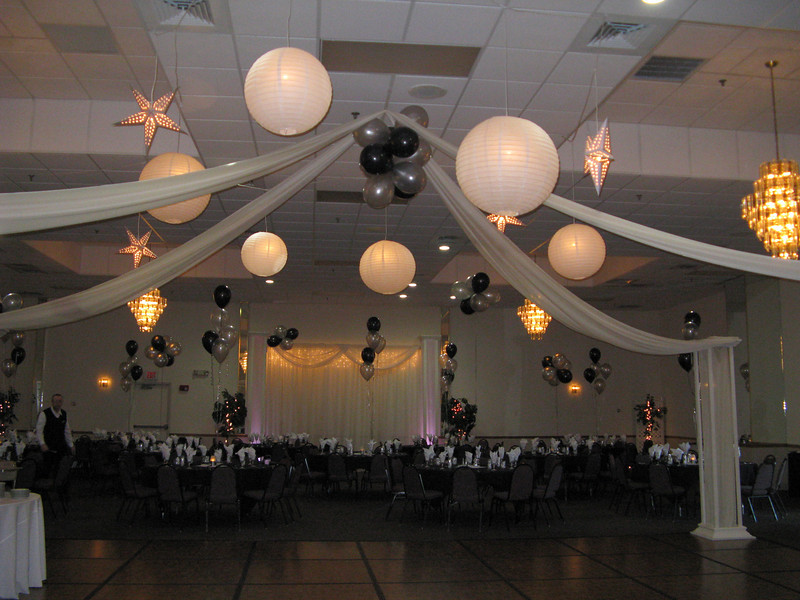 Dance Canopy- White lighted hanging lanterns and silver star hanging lanterns with a balloon center.  This was a Prom dance floor, but it could be modified for a wedding by taking out the balloons and the stars and using more white lanterns or lanterns in the bridal colors.  This is the look with 10 lanterns.  We can put up to 40 lanterns on your dance floor, with or without the draping,  for a beautiful effect.  This also looks particularly beautiful in a tent!<br /> Maneeley's in South Windsor