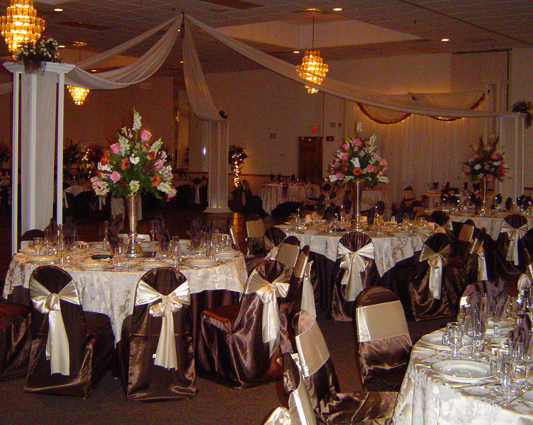 Chocolate and Champagne Wedding - Dance Canopy featuring cream colored roses on each column and a brown silk drapery tassel in the center.  The backdrop has an extra swag of chocolate material to match the decor. The chaircovers, napkins and floorlength tablecovers are chocolate brown.  The sashes and overlays are cream colored silk. <br /> Maneeley's in South Windsor, CT