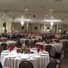 Tulle Dance Canopy- Victorian Christmas Party.  This canopy was made with sparkle tulle and burgundy ribbon with a burgundy poinsettia and cream colored rose Kissing Ball.  This type of dance canopy could be used to add extra bridal color to your wedding decor. They used this style of canopy because the party was over 500 people and they were showing a video presentation as well as giving speeches.  We were trying to give as clear a line of sight as possible while still getting the dance canopy effect.<br /> Maneeley's in South Windsor