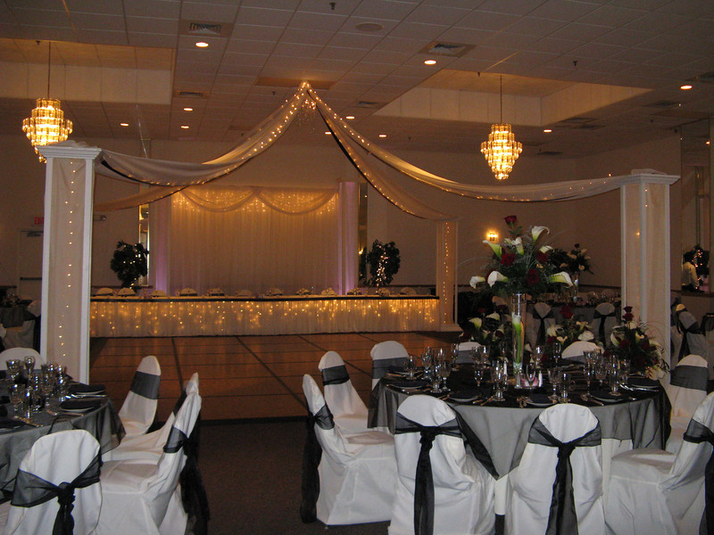 "Black and Ivory Wedding- Lighted canopy with a black ribbon detail. Notice the twinkle lights in the canopy that carry down the columns.  The bride was afraid the black would look too dark, so she wanted lots of lights to make it sparkle.  The head table, cake table and gift table were also lighted with a simple black ribbon detail.  The table covers and chairs are ivory with black organza overlays and black organza bows tied in a Windsor knot.  The center is crystals hung in a circle with twinkle lights.  The bride wanted something ""sparkly"".  The gorgeous florals are by Broadbrook Gardens and they are a single calla lilly in a lighted pilsner vase with roses and calla lillies and bear grass.  <br /> Maneeeley's in South Windsor, CT"