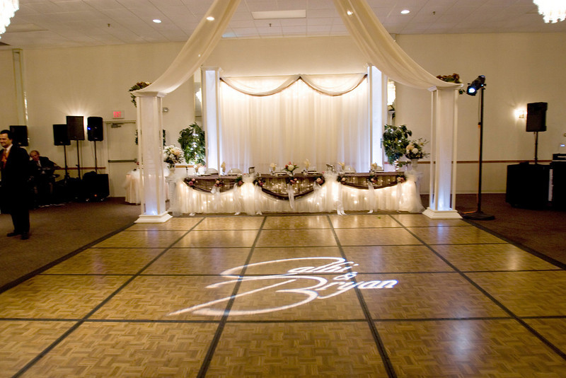 Fall Dance Canopy- A wide shot of the dance canopy and decorated head table.  The gobo in the center of the dance floor added a lot to the design. The head table is decorated with brown silk and the family brought the pew bows back from the church and hung them on the front of the table.  The backdrop has a swag of chocolate brown tulle to carry the color scheme. Picture by CTM Photography.<br /> Maneeley's in South Windsor