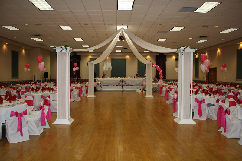Fuschia and White Vietnamese Wedding- This huge dance floor was made more intimate with a white dance canopy.  The kissing ball was fuschia flowers with greenery and ivy trailed down from the top of each column.  There were 270 people at this wedding.  I also did the white chair covers and fuschia silk sashes.  The balloon decor and head table decorations were created by Alma Magic.<br /> Springfield Elks in Springfield