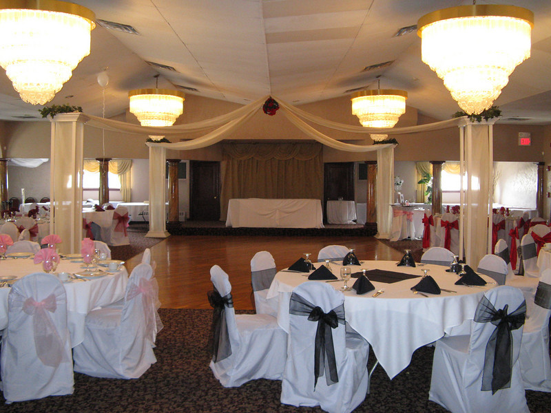 After the Dance Canopy-  This is before the Bridal Show, so the tables and chairs are set with different styles and colors to highlight different options.  The kissing ball is ivy and red roses and the columns are topped with ivy.  Many other options are available.  <br /> Georgina's in Bolton