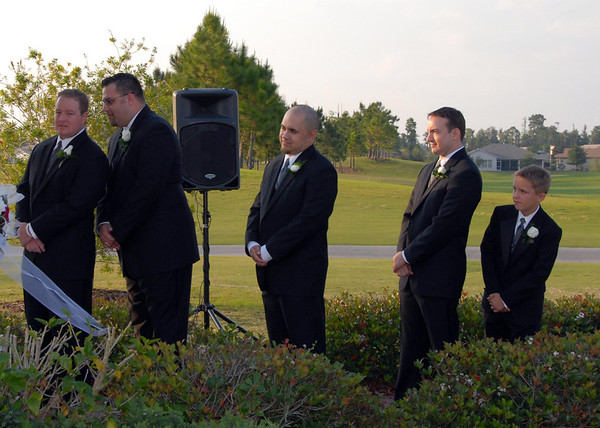 The groomsmen try to get a better view of the entering bridesmaids.