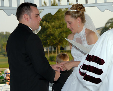 Kim puts the ring on Dave's finger while making her vows.
