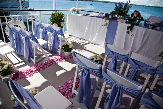 White wood chairs by Lakes Area Rental, chair ties by BBJ, floral by Pesche's; aboard the upper deck of the Duchess.