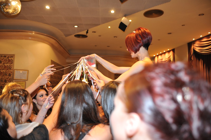 "The next secuence of pictures shows a traditon in Argentina. All the single women have to hold one of the ribbons, and when the bride count till 3, the girls pull the ribbons out of the holder, and the one that gets the  ""ring"",(its a fake one dont get exited, hehe), it suppose to be  the next person getting married.<br /> ~Eva~"