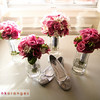 The bride's CUTE shoes, surrounded by her and her bridesmaids' bouquets.